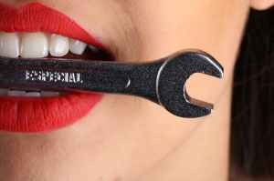 Woman holding a wrench in her mouth