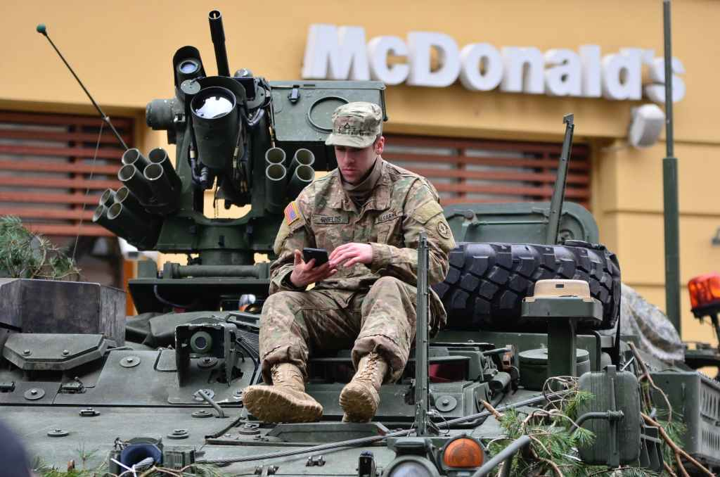 Soldier on tank in front of McDonalds